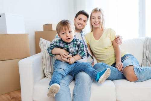 Junge Familie auf dem Sofa - gute Erziehung kann erlernt werden.